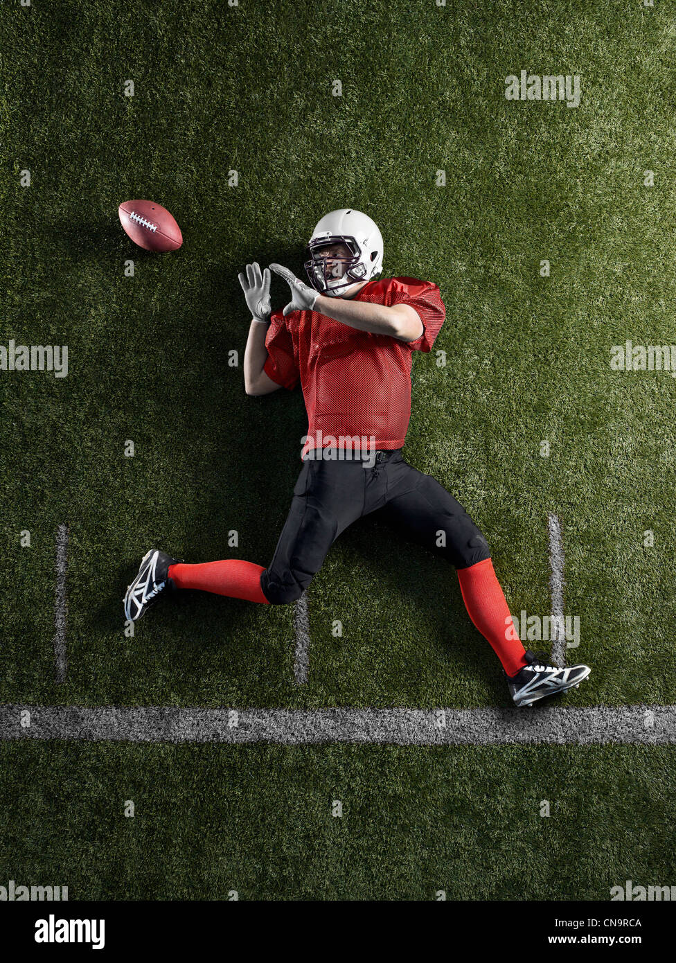 Football player laying on field - Stock Image
