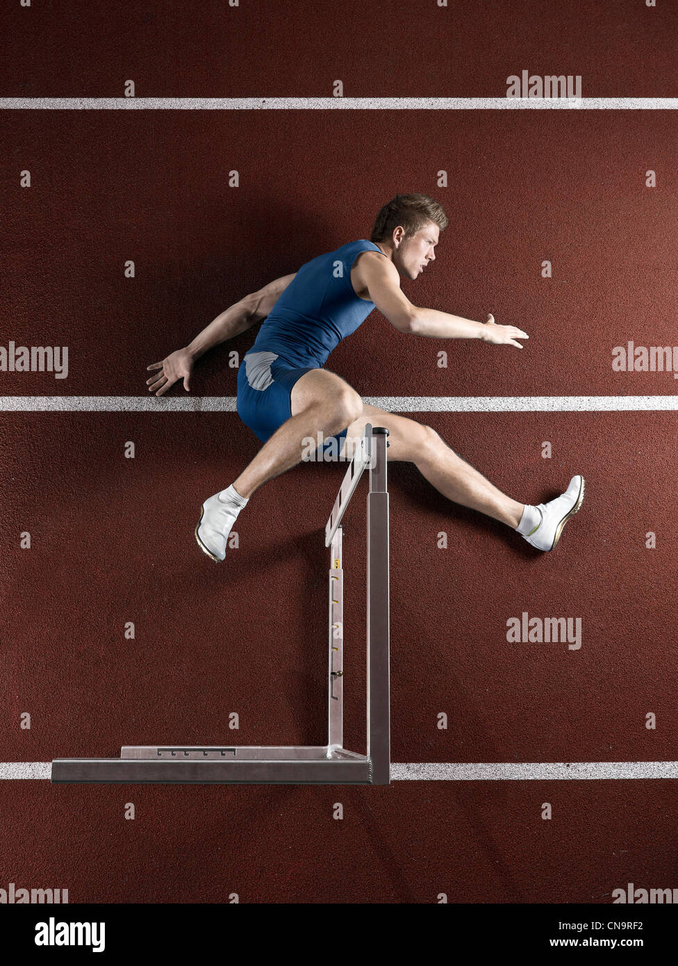 Runner laying with hurdle on track - Stock Image