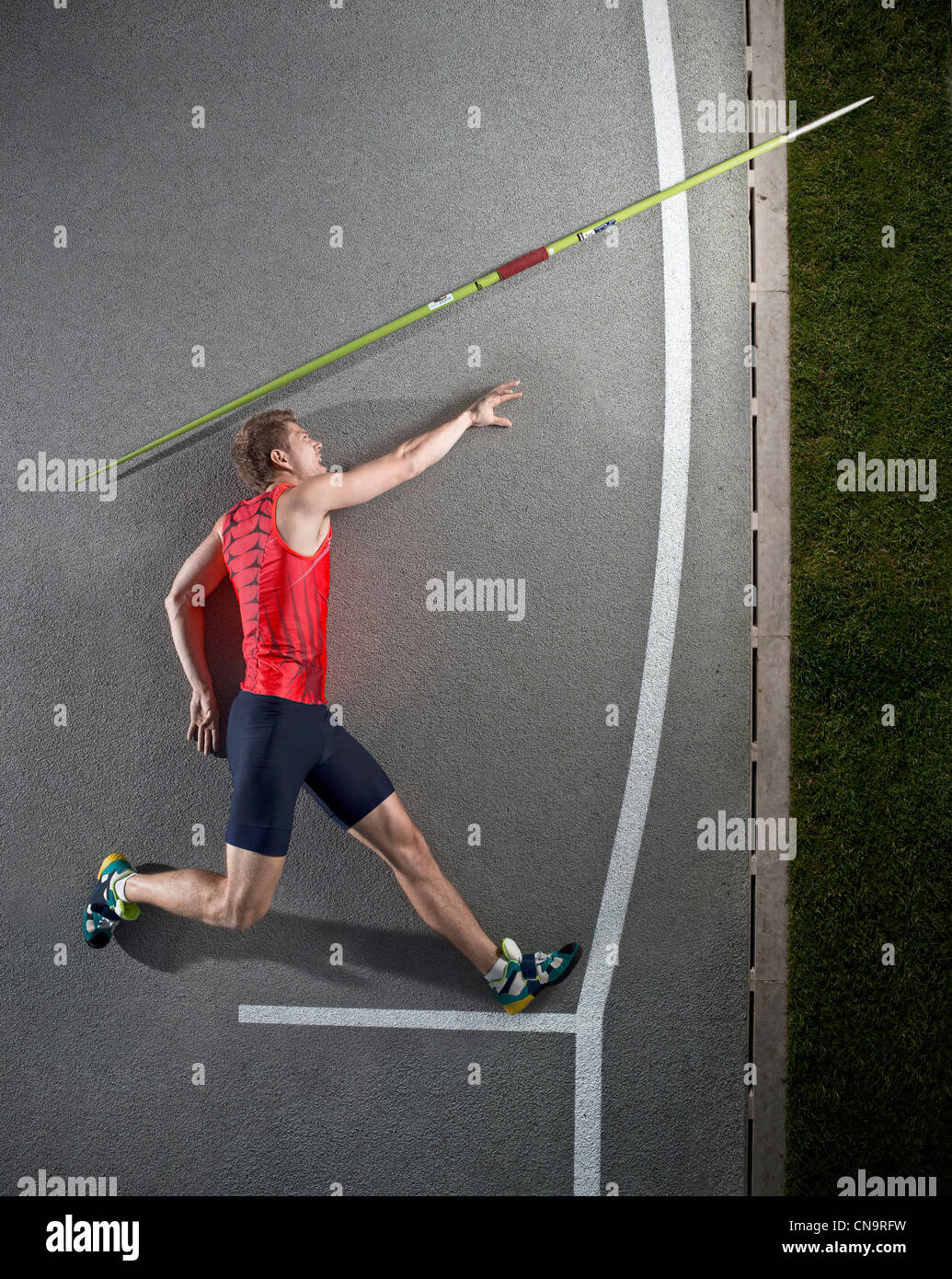 Javelin thrower laying on track Stock Photo