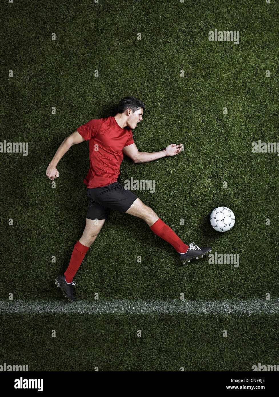 Soccer player laying on pitch - Stock Image