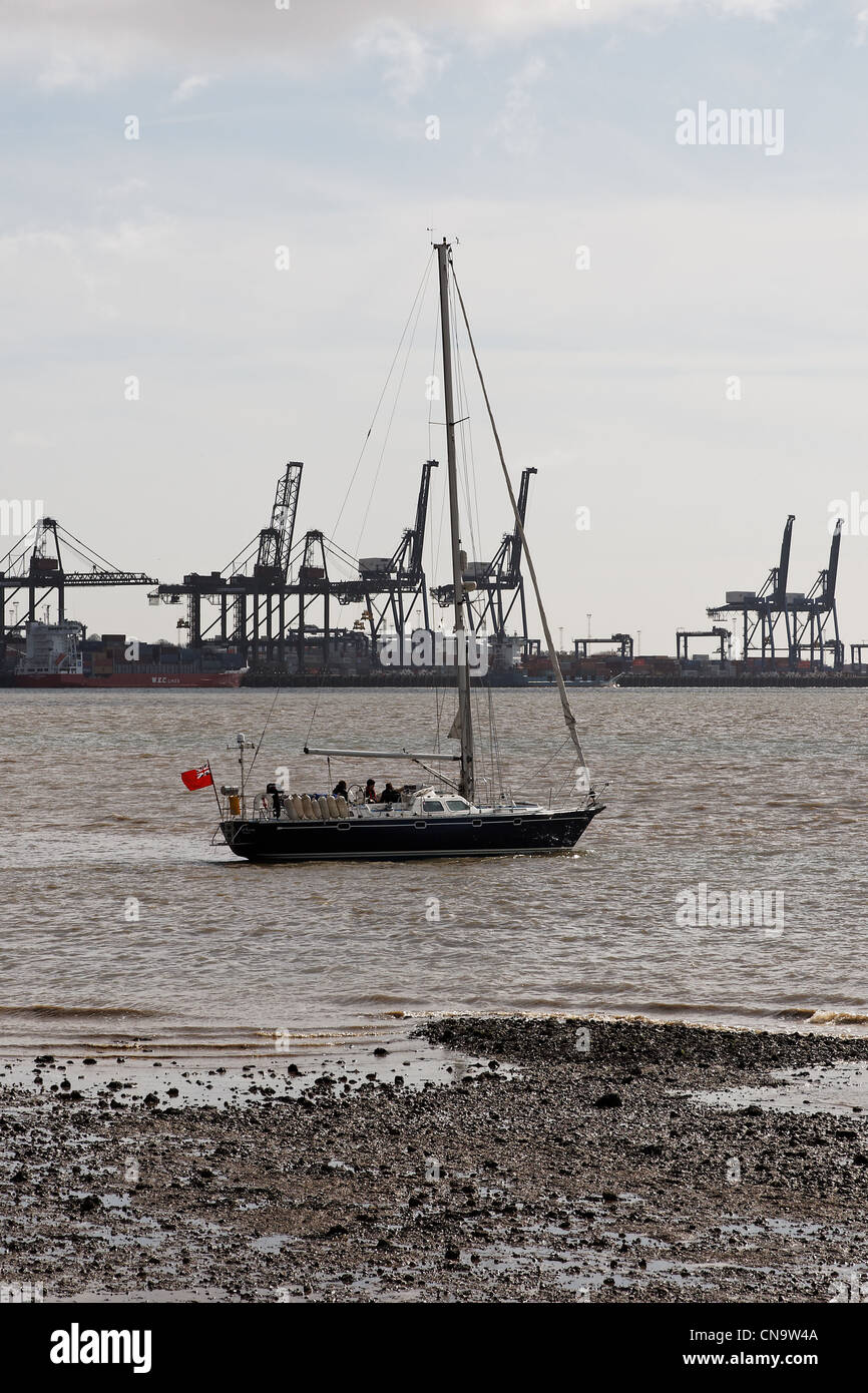 A sailing yacht aground in Harwich Harbour, UK with Felixstowe Container Terminal in the background - Stock Image