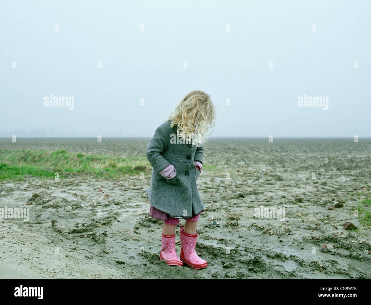 Girl wearing rainboots on beach - Stock Image