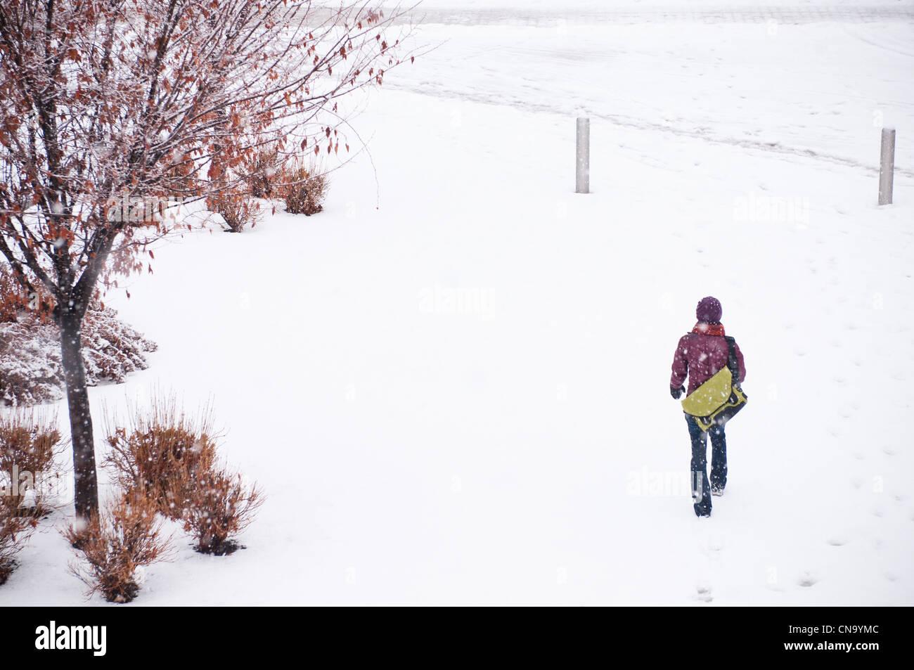 Woman walking in snowy meadow - Stock Image