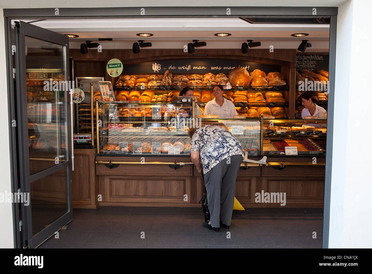 German bakery in Bamberg with all sorts of bread. old woman bent searching for money to pay - Stock Image