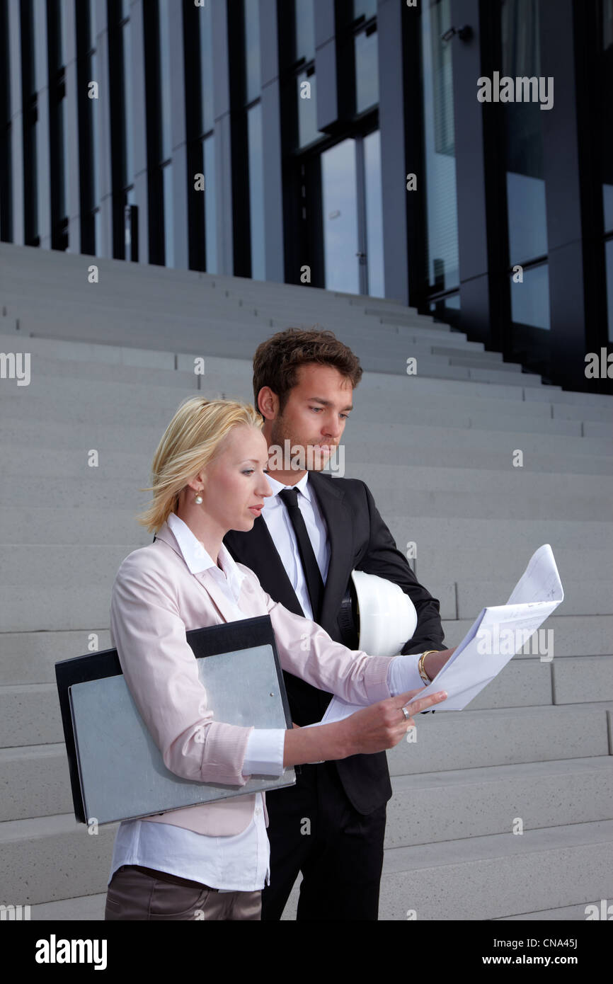 man and woman with plan standing on stairs - Stock Image