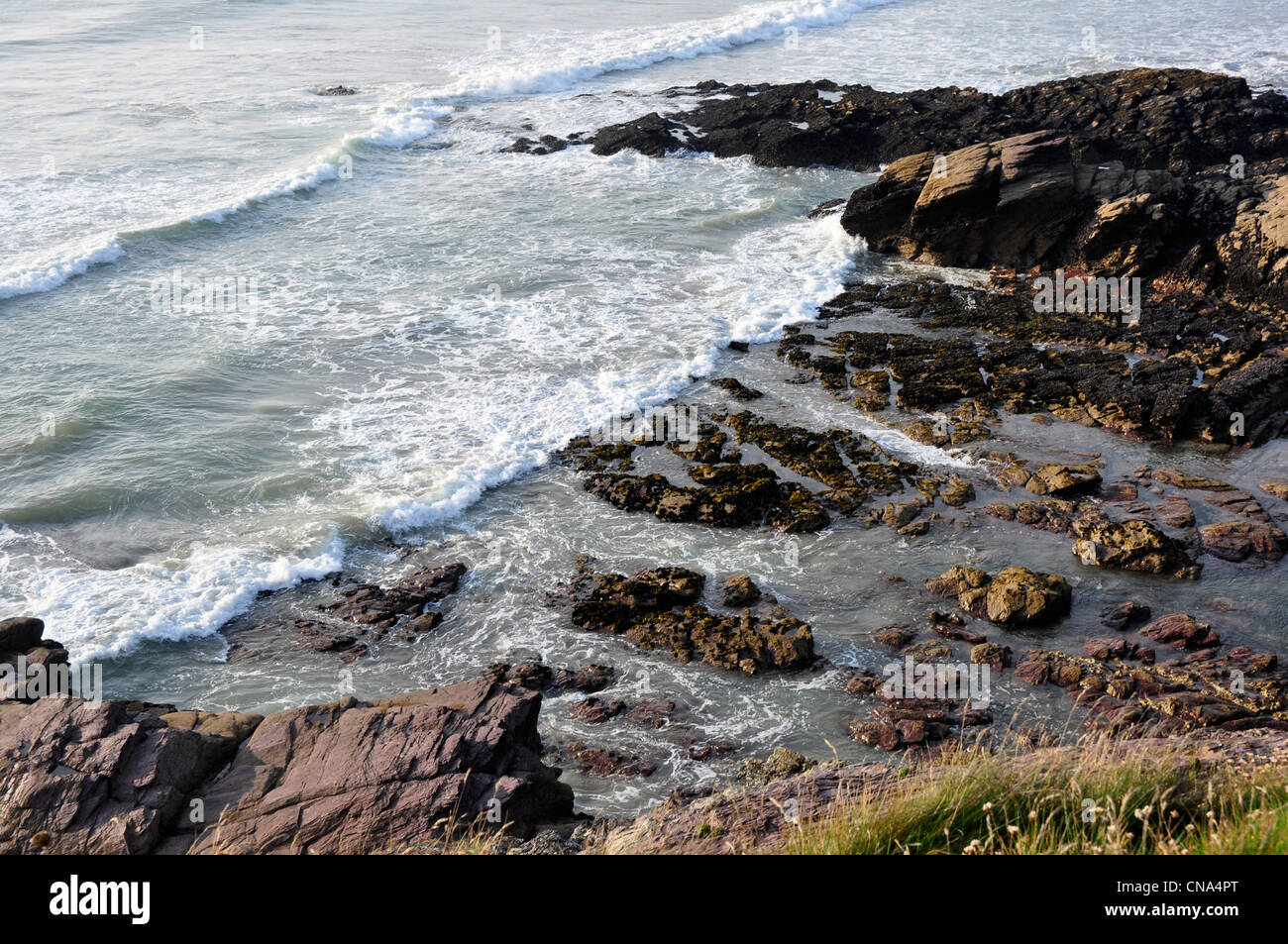 Cornwall - rocky beach and incoming tide - white flecked waves - seen from the cliff path at Polzeath - Stock Image