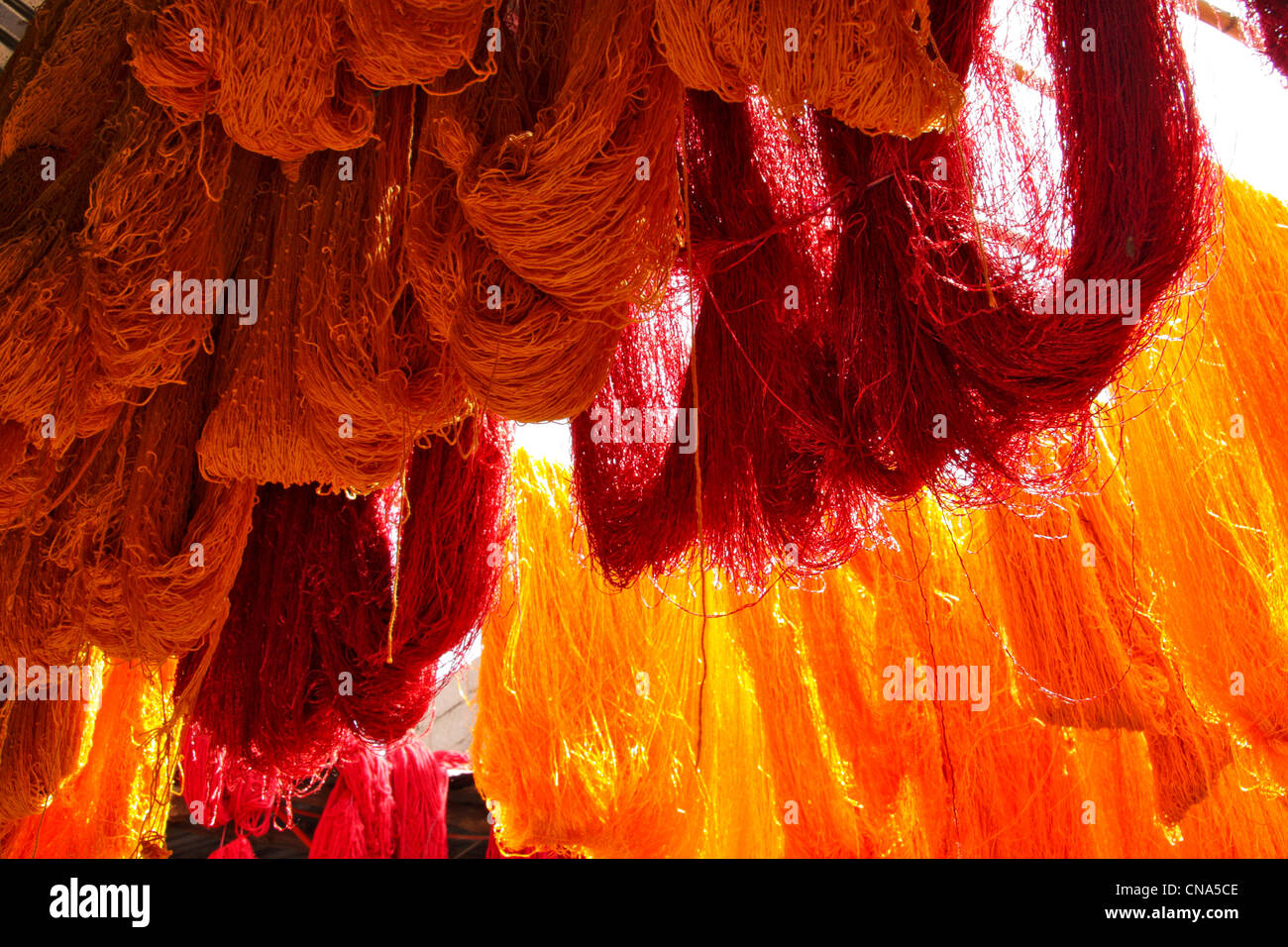 Freshly dyed red and orange skeins of wool hang drying in the sunlight at the Wool Dyers souk in the medina, Marrakech,Morocco Stock Photo