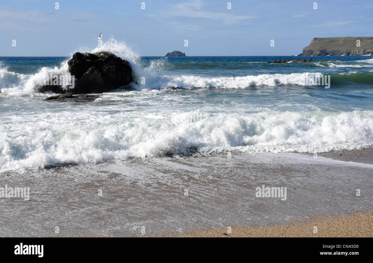 Breaking rollers on a lone rock, blue sky, white crested waves on a Cornish beach - Stock Image