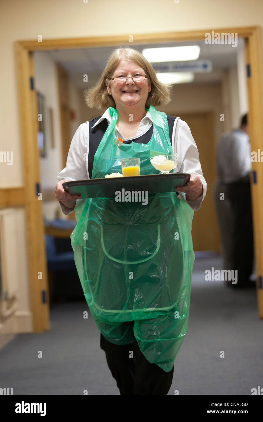 A woman carries a meal down a corridor in hospital UK Stock Photo
