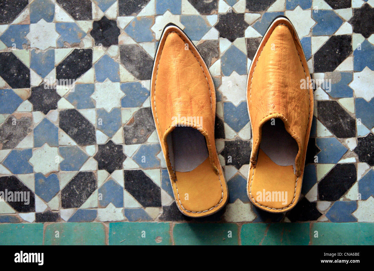 A pair of traditional Moroccan slipper-shoes (babouches) against traditional mosaic tilework (zellij) in Marrakech, - Stock Image