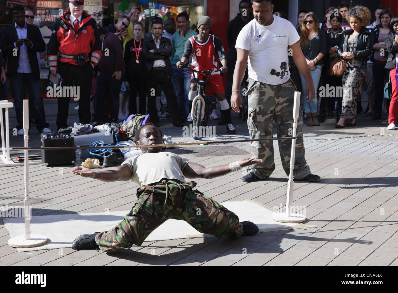 Street entertainers limbo dancing under a low pole with an audience of people watching in Leeds city centre Yorkshire - Stock Image