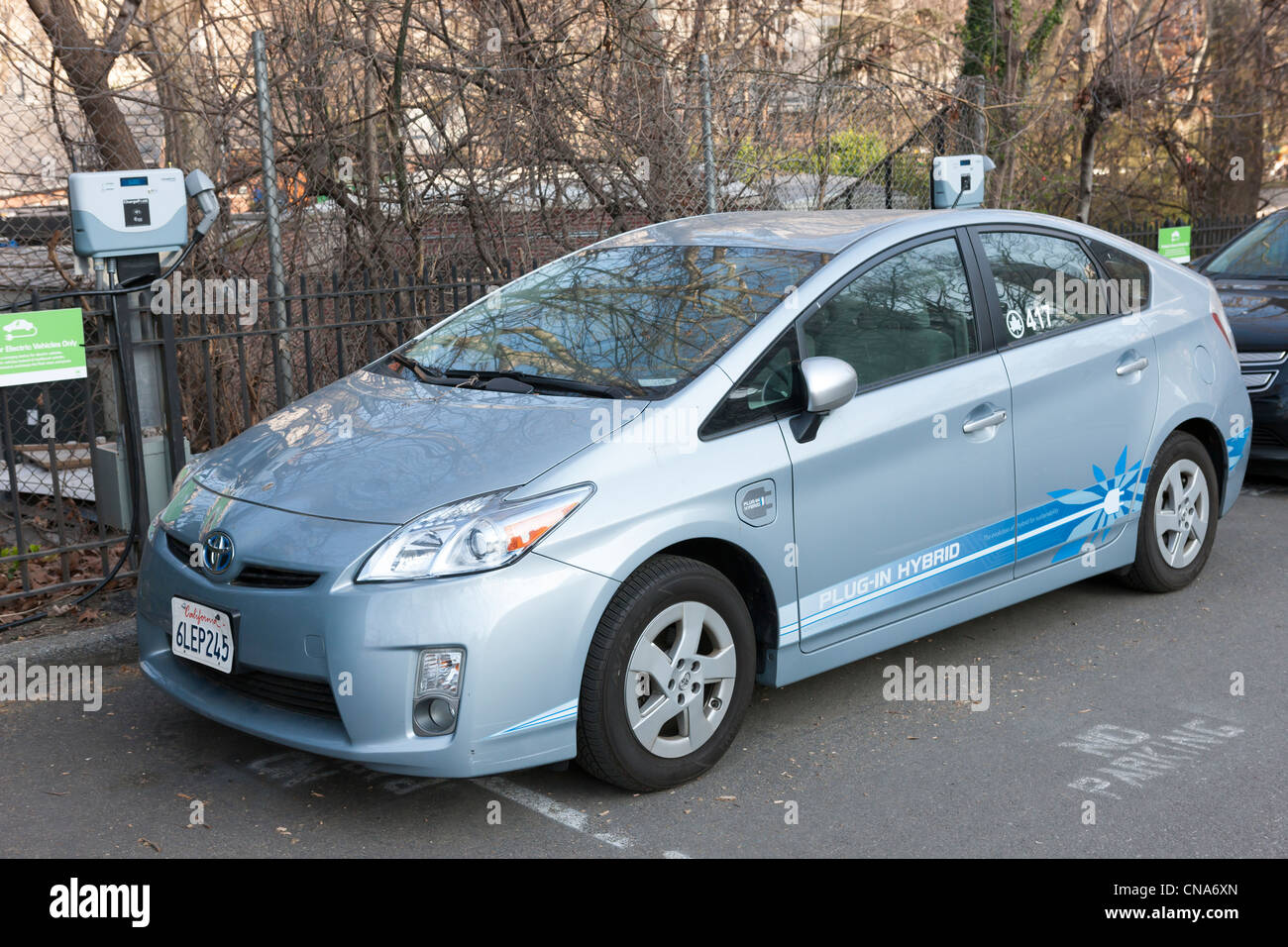 A Toyota Prius hybrid electric car, used by the New York City Parks department, receives a charge at a charging - Stock Image