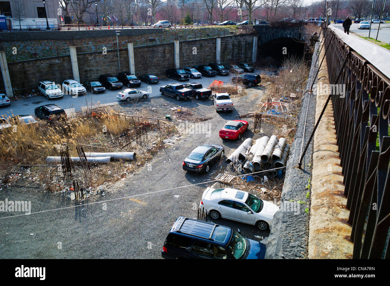 Open vacant below grade lot used for parking and filled with litter and debris in center city Philadelphia, Pennsylvania, - Stock Image