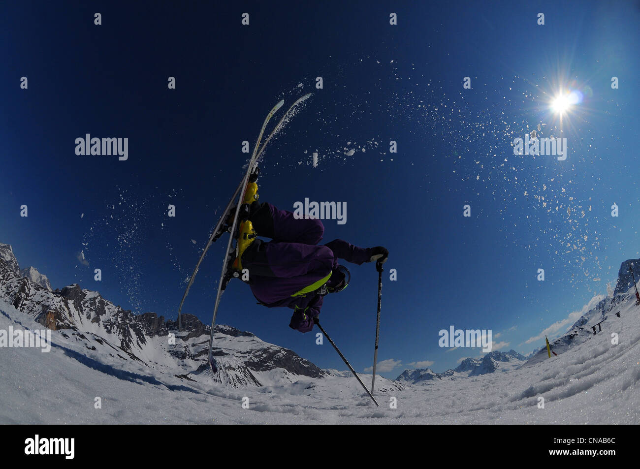 A skier performs a flip using his poles in the ski resort of Courchevel in France. - Stock Image