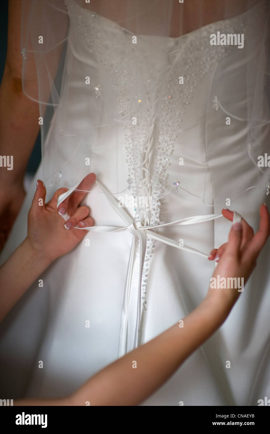 tying the bow on the back of a wedding dress worn by a bride - Stock Image