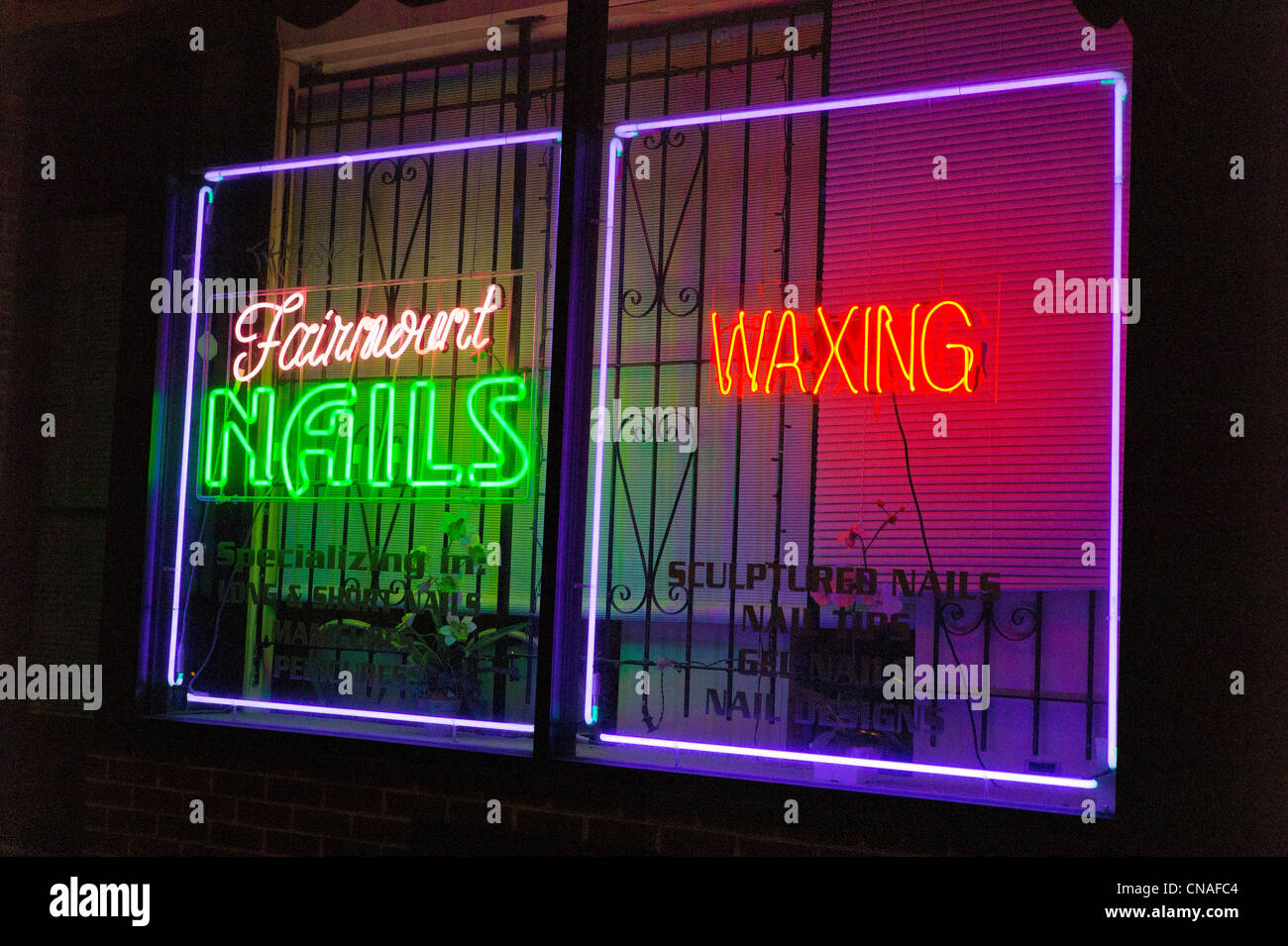 Neon signs lit at night in the window of a nails & waxing shop, Philadelphia, Pennsylvania, USA - Stock Image