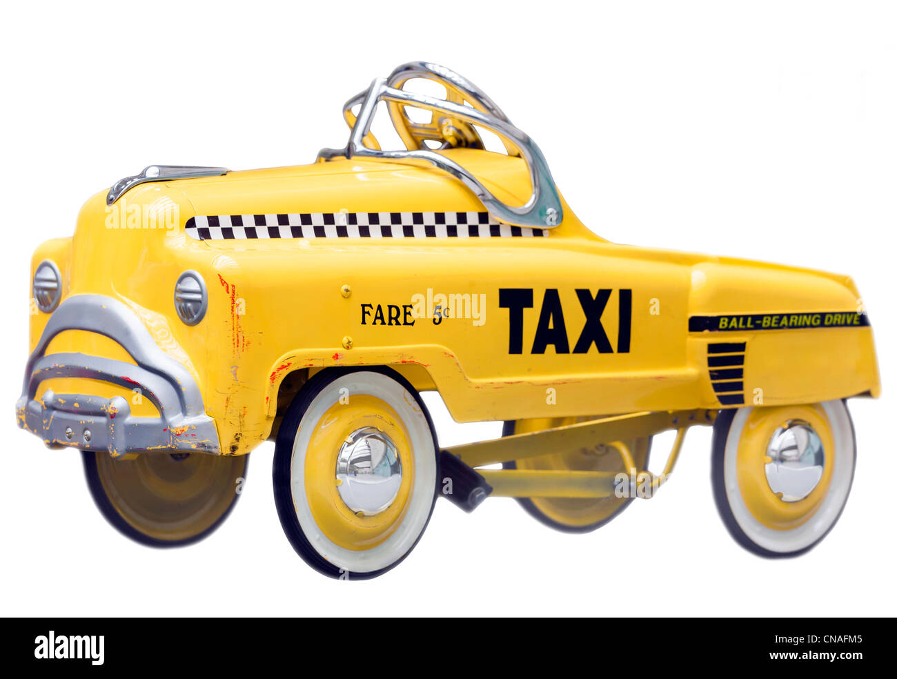 Kid's size small version of a vintage Yellow New York Taxi Cab. A push bike pedal car. Cut out isolated on a - Stock Image