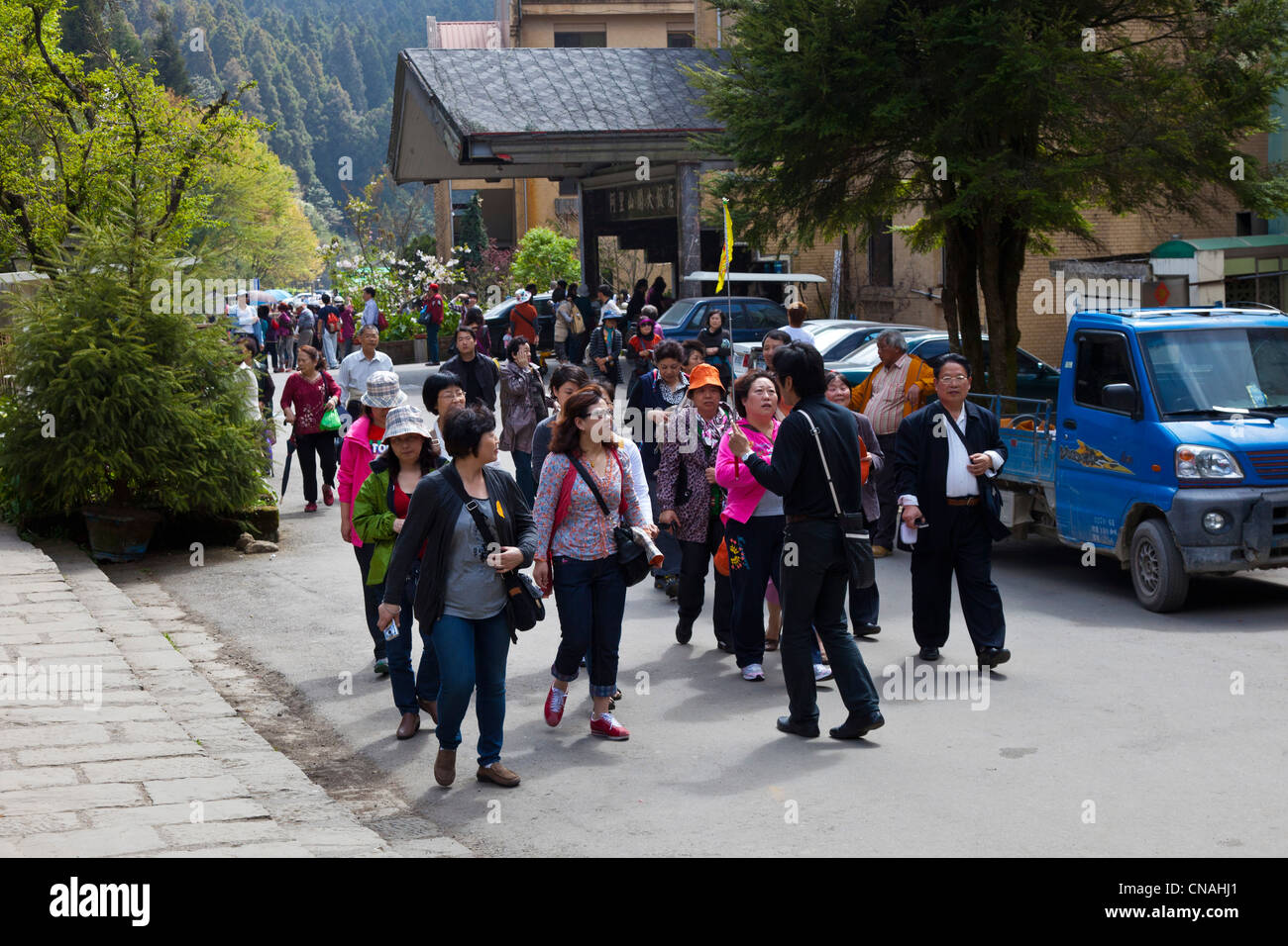 Party of tourists from mainland China with tour guide outside Alishan Gou Hotel in Alishan Taiwan. JMH5912 - Stock Image