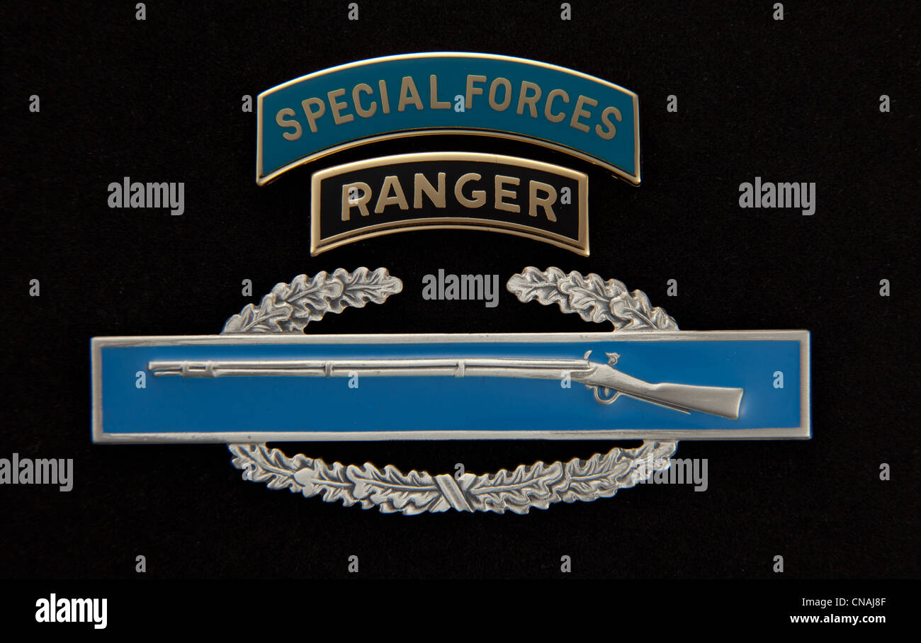 US Army Special Forces and Ranger dress tabs over a Combat Infantry Badge (CIB) on black - Stock Image
