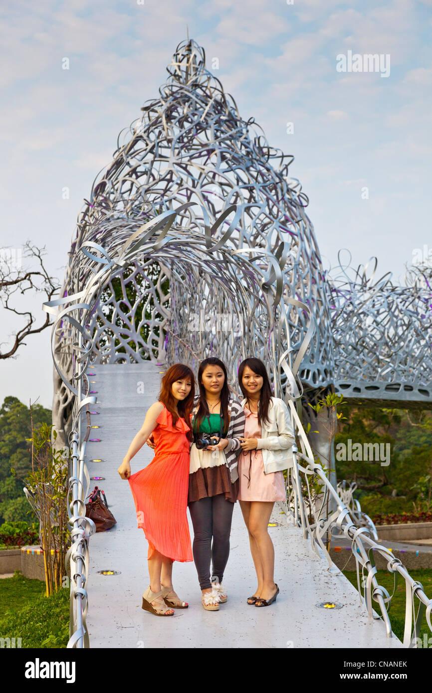 Three young local Taiwanese women on Rippling Moonlit Talk Bridge, Chiayi, Taiwan.  JMH5957 - Stock Image