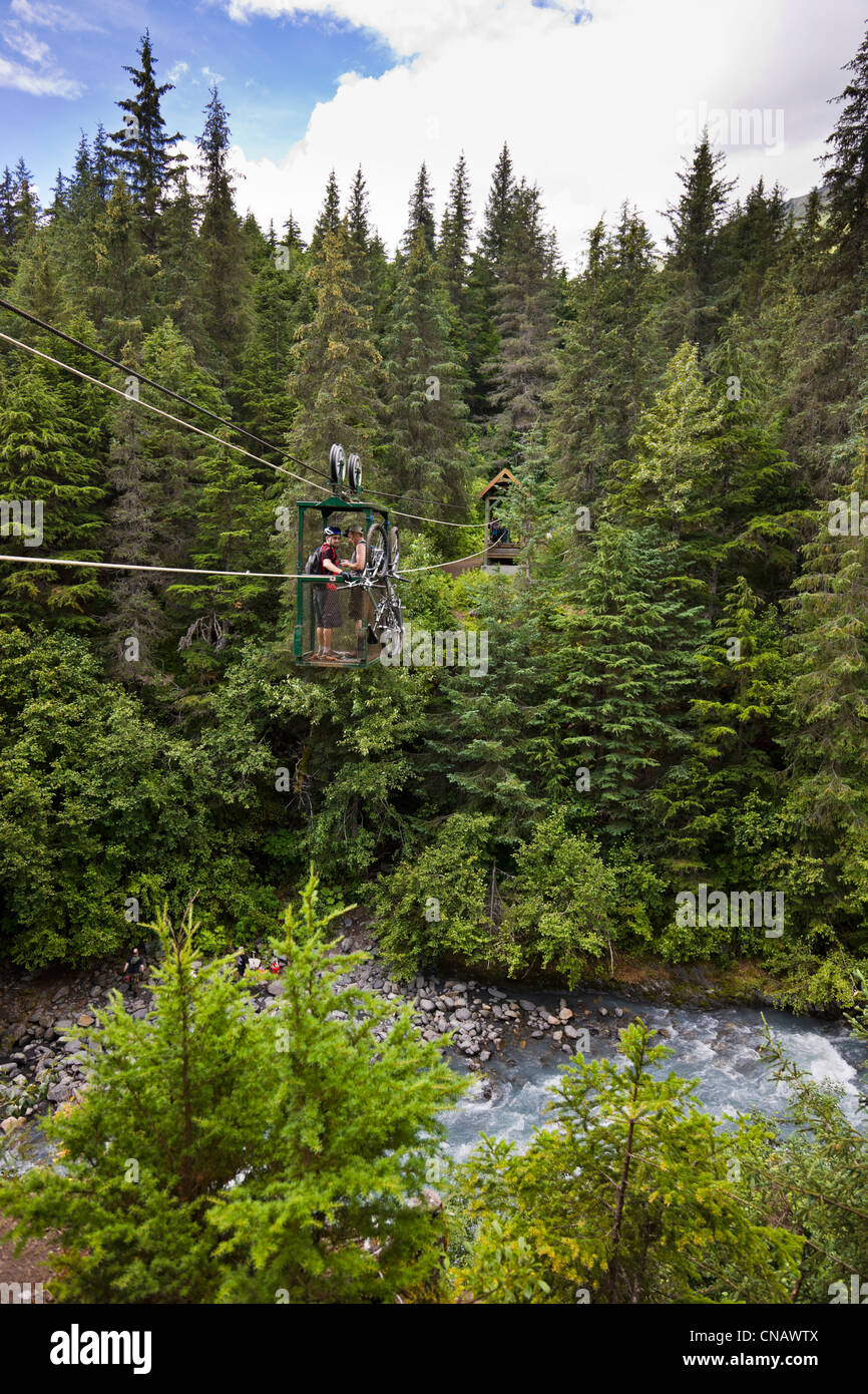 Mountain Bikers riding the hand tram over Winner Creek near Girdwood, Southcentral Alaska, Summer - Stock Image