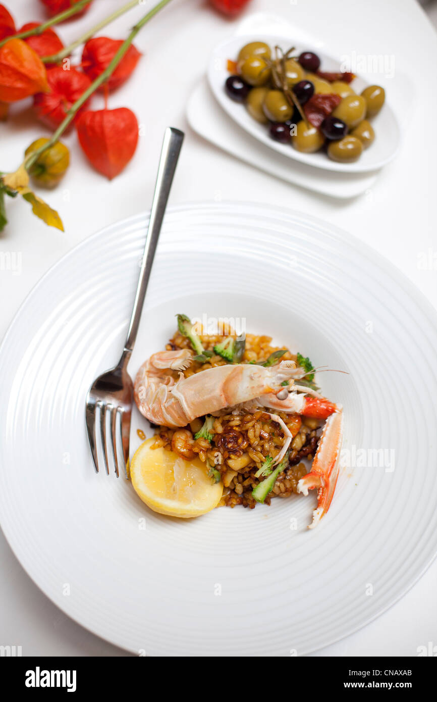 Plate of langoustine paella with olives - Stock Image