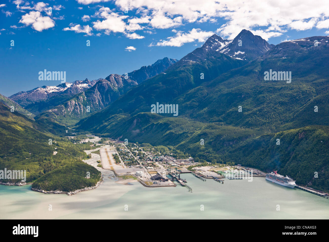 Aerial view of the city of Skagway with a cruise ship docked at port, Southeast Alaska, Summer - Stock Image