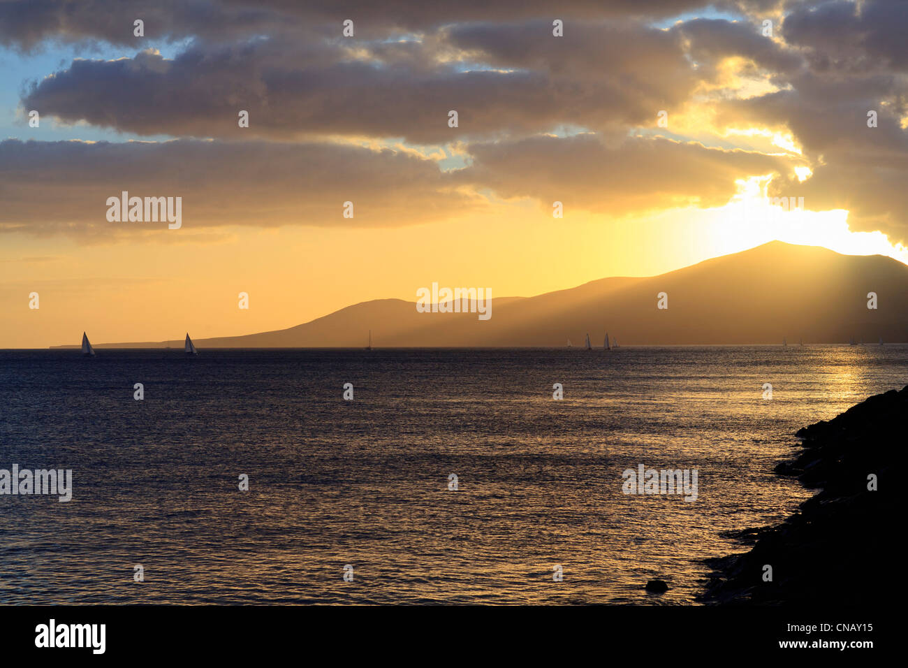 Sun setting over mountains and water - Stock Image