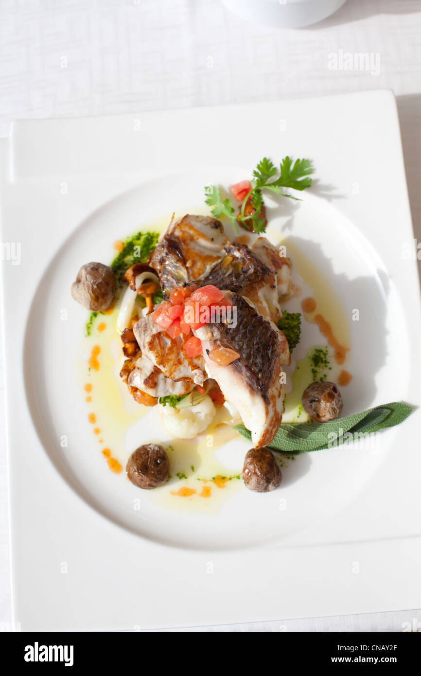 Plate of fish on restaurant table - Stock Image