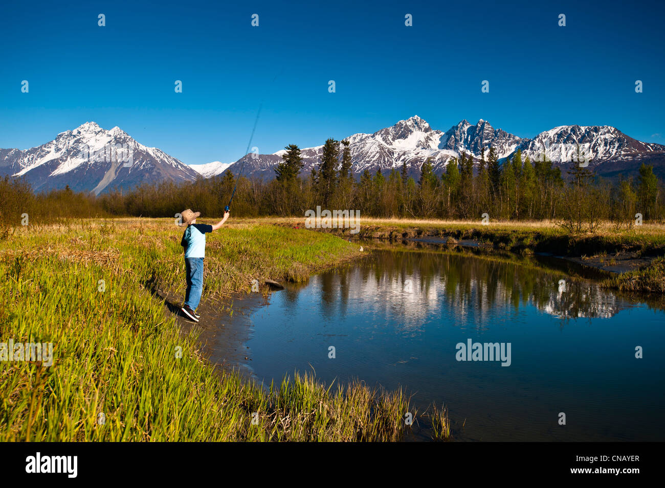A young boy fishing on Rabbit Slough on a sunny spring day in the Matanuska-Susitna Valley, Southcentral Alaska - Stock Image