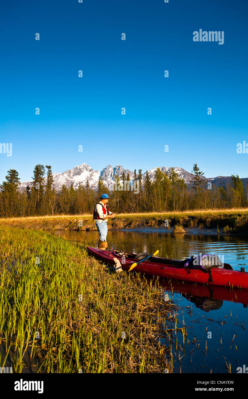 Man with a kayak fishing from the shore of Rabbit Slough in the Palmer Haystack Flats wildlife refuge, Mat-Su Valley, - Stock Image