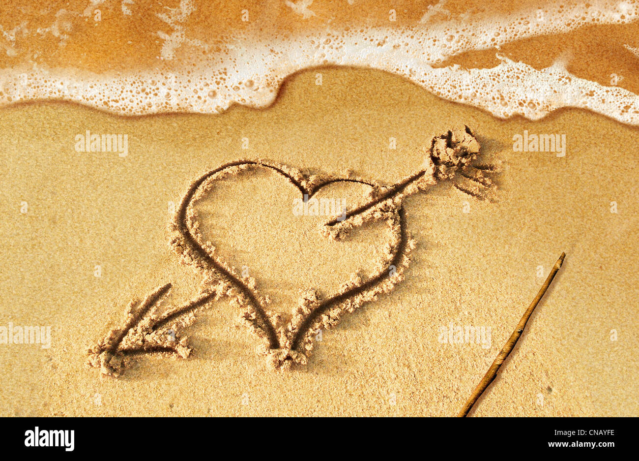 Heart with arrow, as love sign, drawn on the beach shore, with some water and foam coming from the sea. Stock Photo