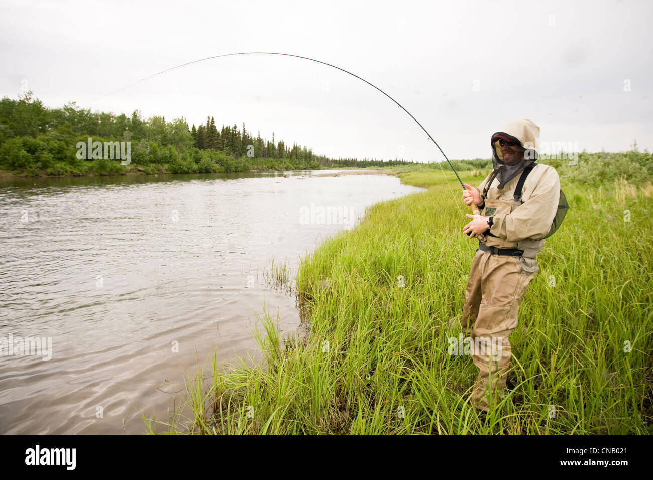 Fly fisherman wearing mosquito protection fishes for salmon on the Mulchatna River in the Bristol Bay area, Alaska Stock Photo