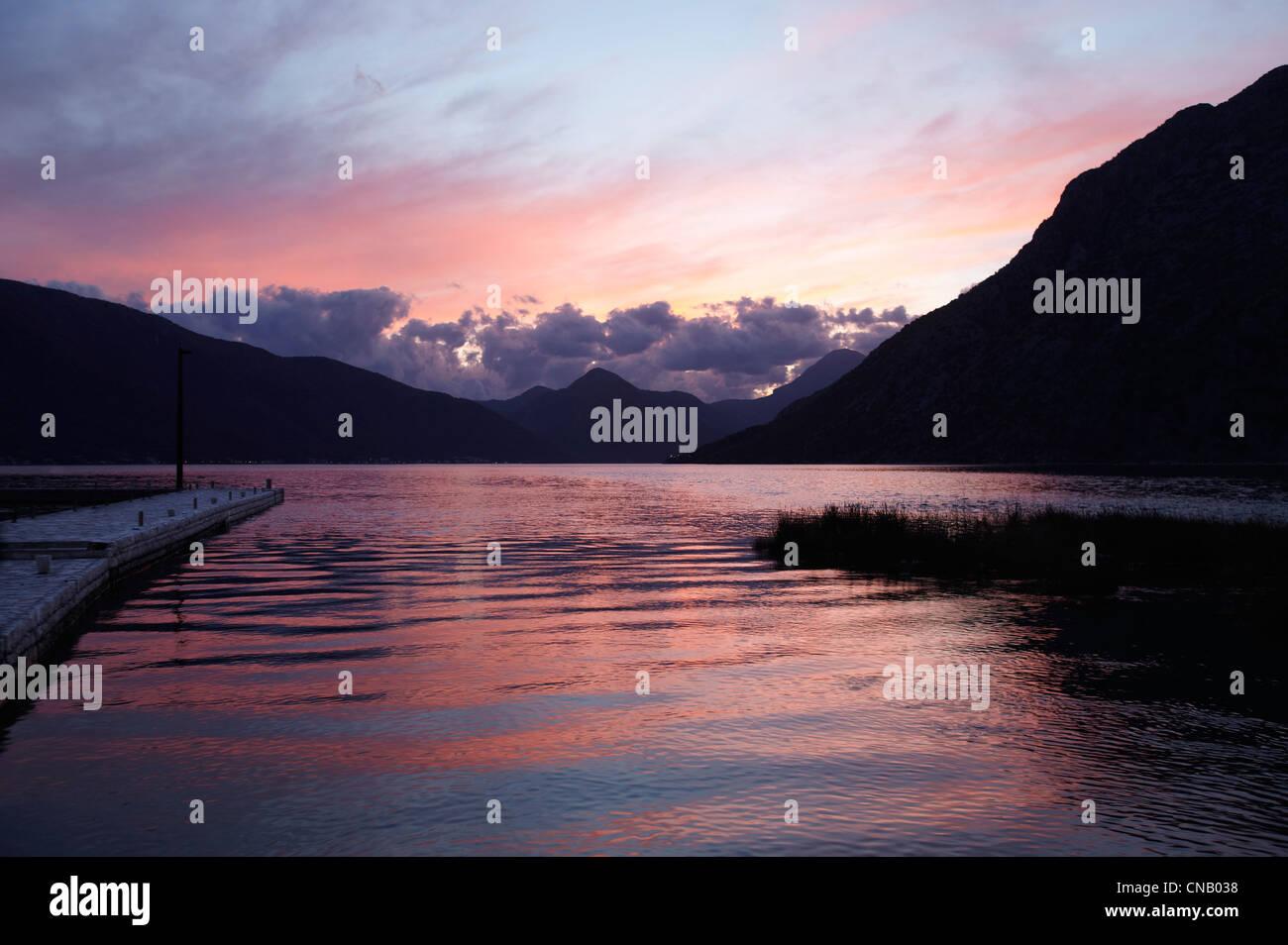 Sunset sky reflected in still lake - Stock Image