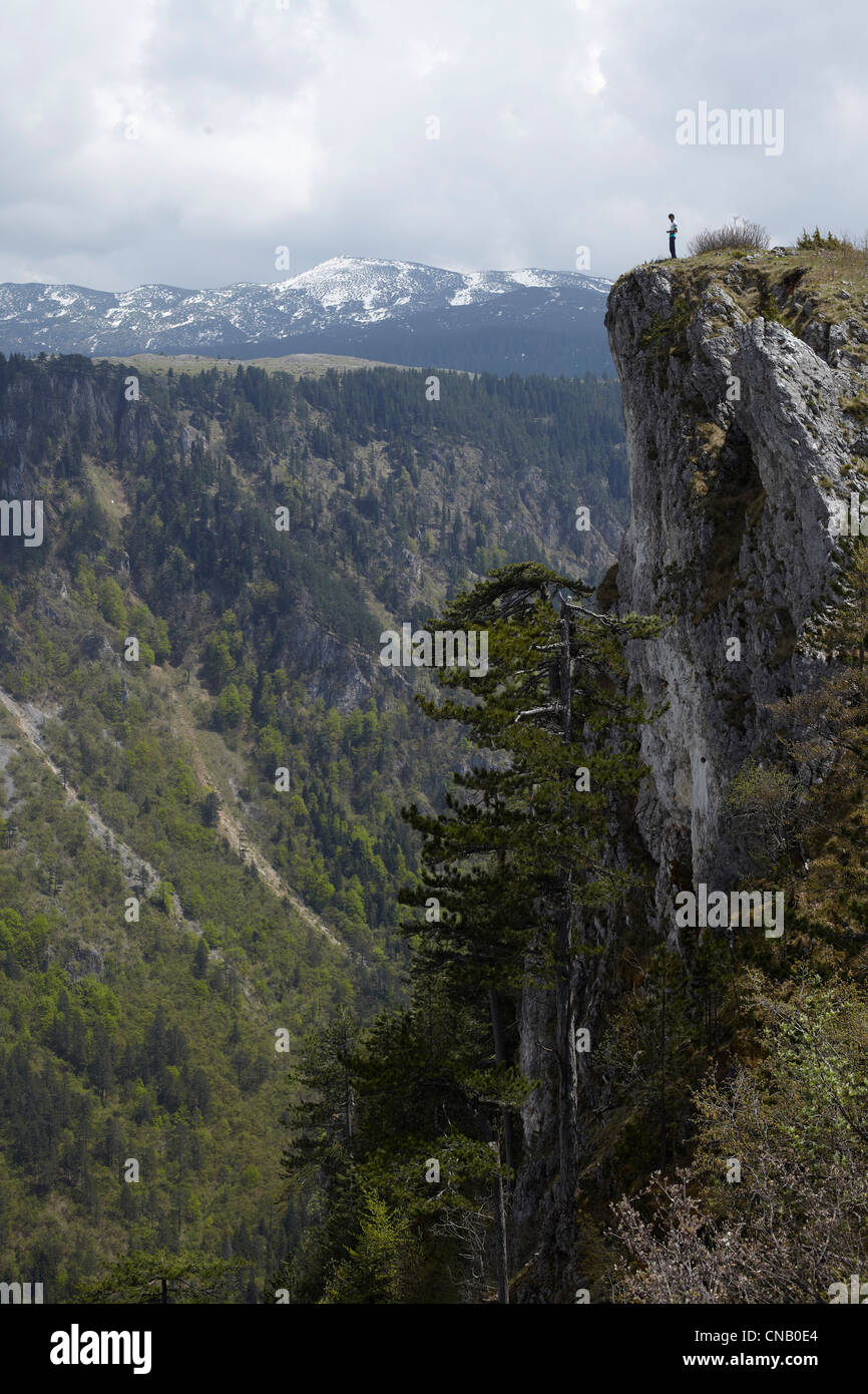 Man standing on rocky cliff - Stock Image