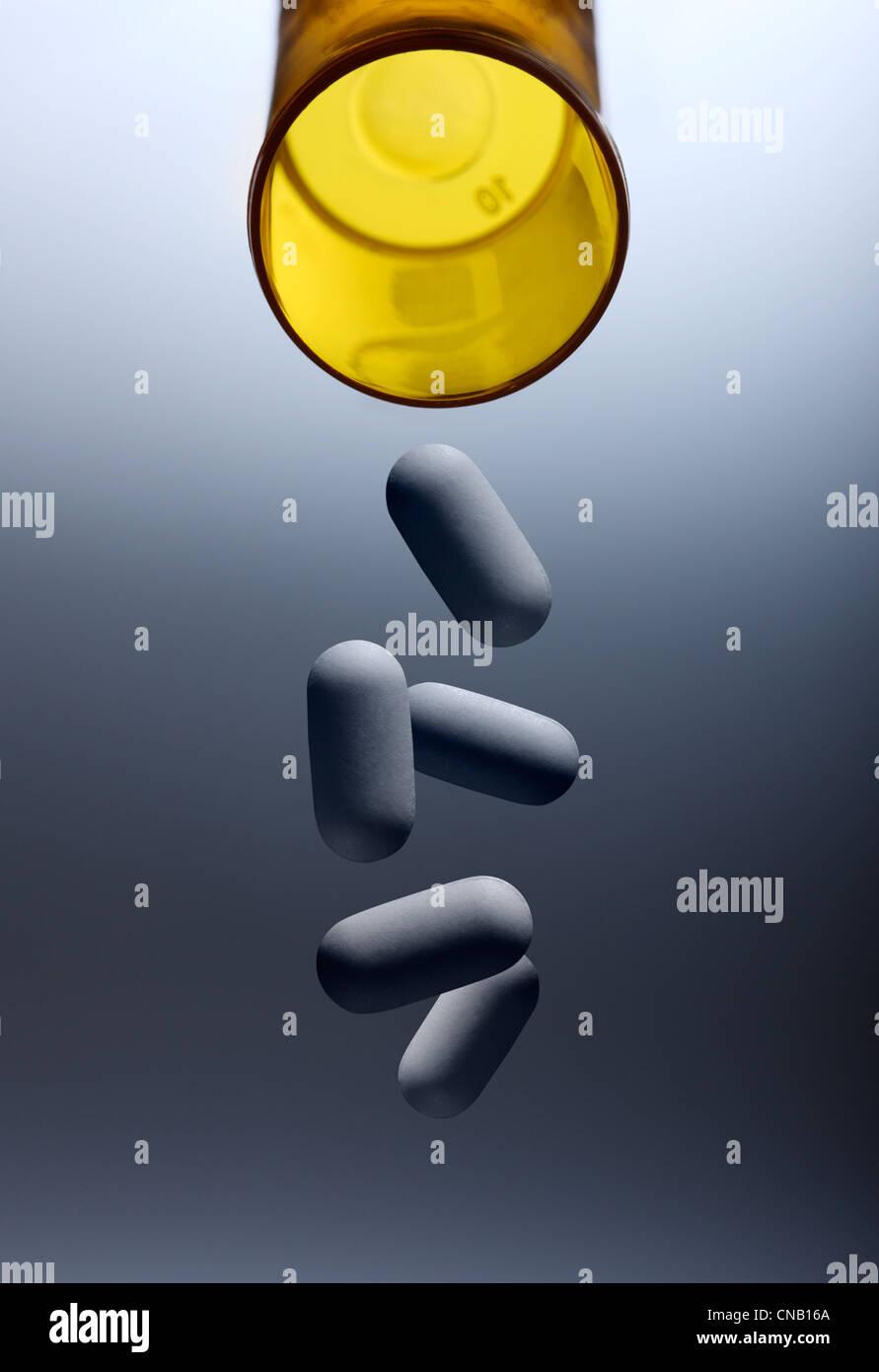 Pills pouring from prescription bottle - Stock Image