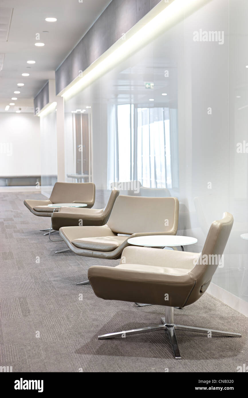 white glass wall beige chairs corridor city office - Stock Image