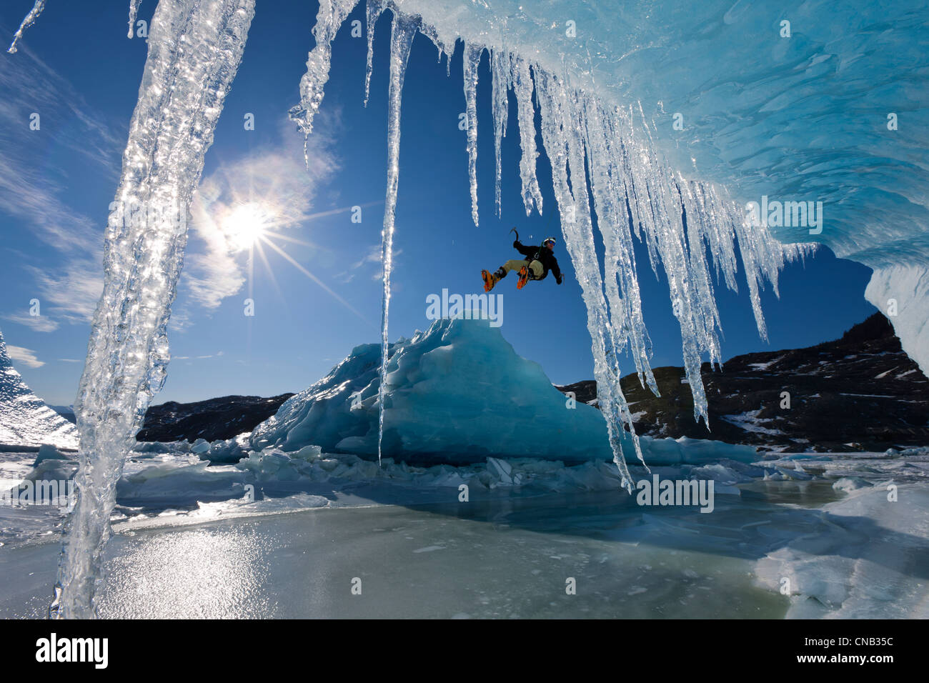 COMPOSITE: Sun shines through icicles hanging on an iceberg as an ice climber rappels over the edge, Mendenhall Stock Photo