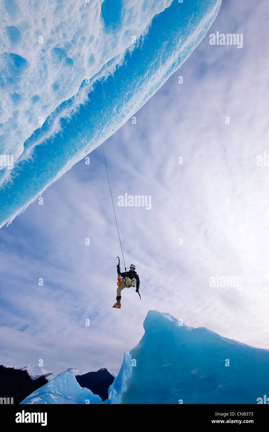 An ice climber swings down from rope to reach face of a large iceberg frozen into Mendenhall Lake, Juneau, Alaska, - Stock Image