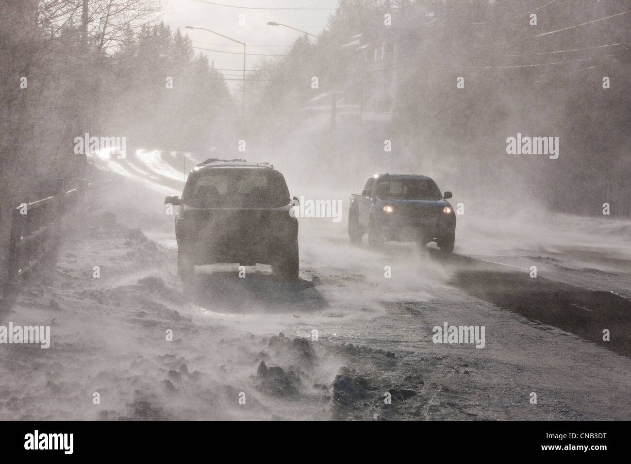 Vehicles drive on Douglas Roadway obscured by 70 mph blowing wind and snow, Juneau, Southeast Alaska, Winter Stock Photo