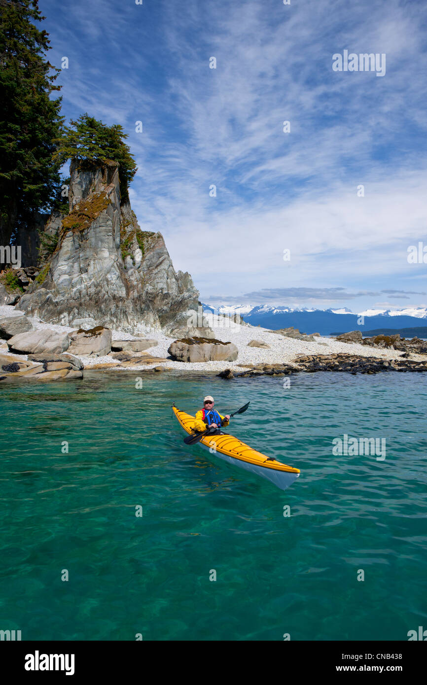 A water level view of a sea kayaker paddling in calm waters along a shoreline near Juneau, Inside Passage, Alaska Stock Photo
