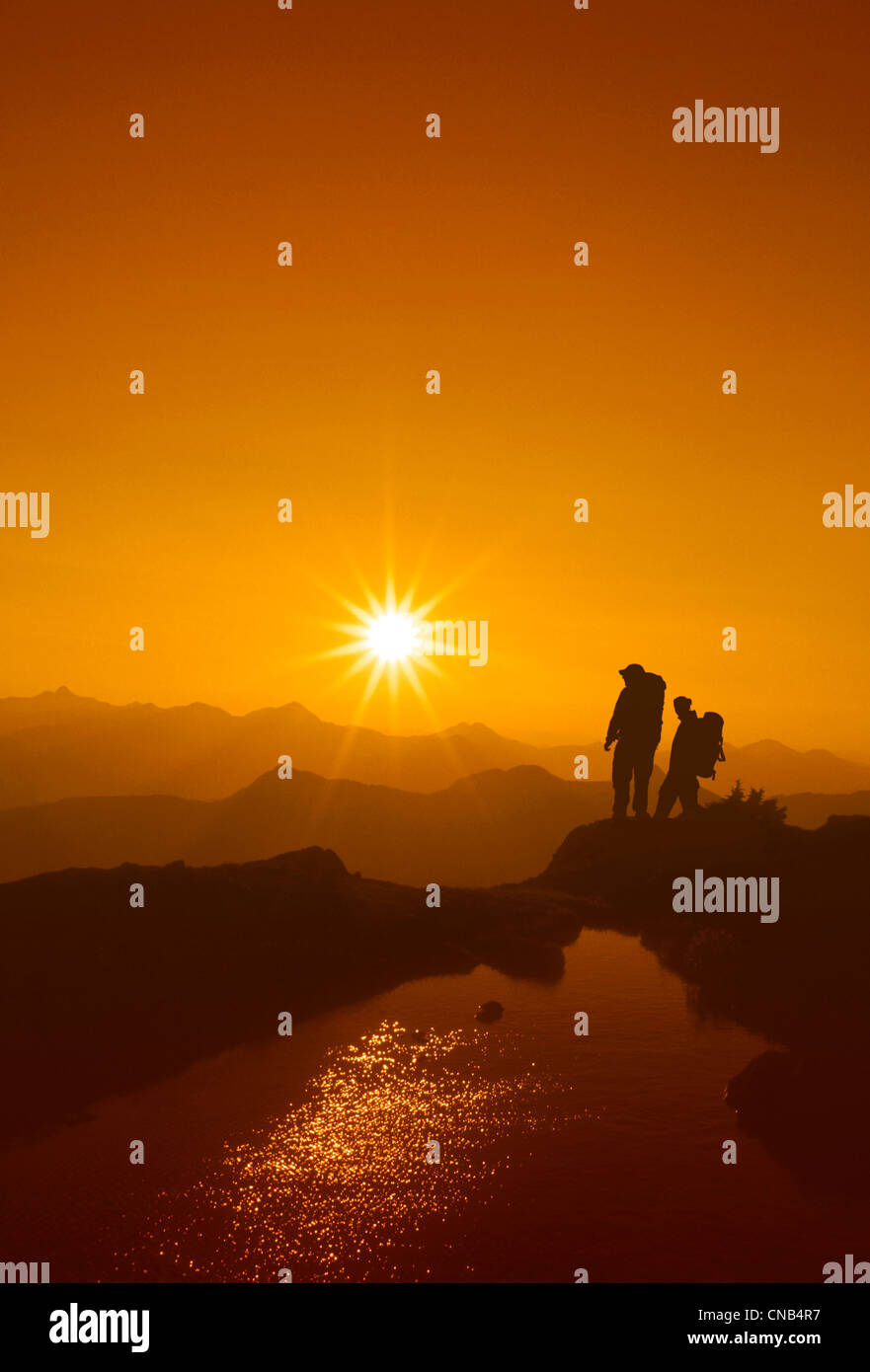 Two hikers watch the sun rise over the Tongass National Forest, Southeast Alaska - Stock Image