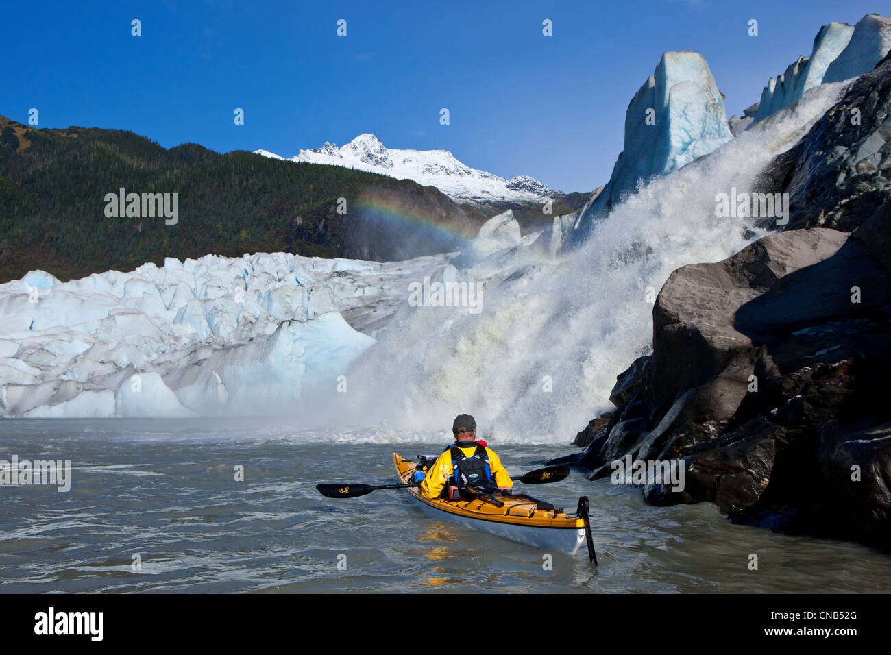 Sea kayaker on Mendenhall Lake with Mendenhall Glacier and Nugget Falls in the background, Southeast Alaska, Summer - Stock Image