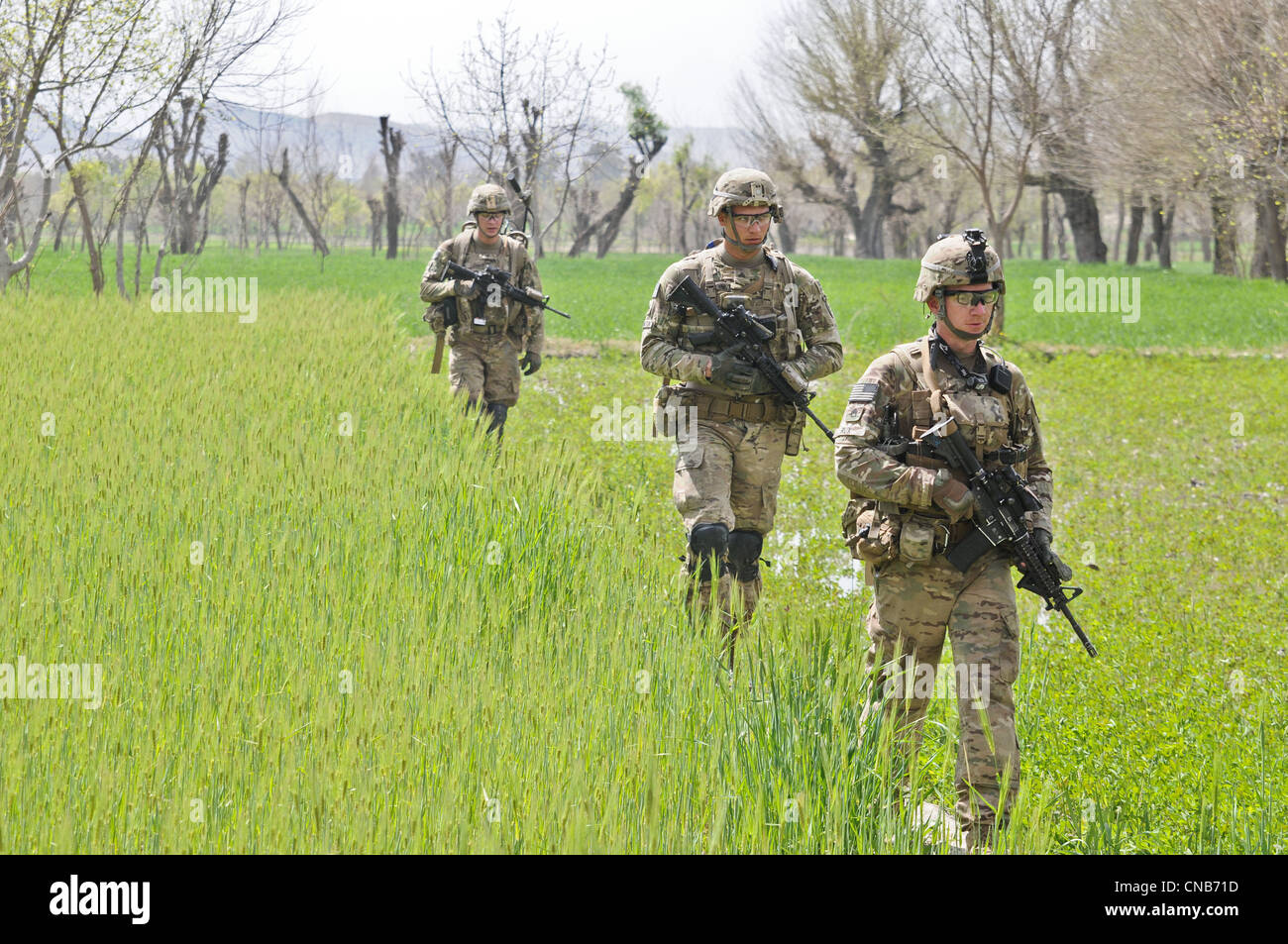 US Army soldiers patrol a field near the village March 30, 2012 in Gorchek, Afghanistan. - Stock Image