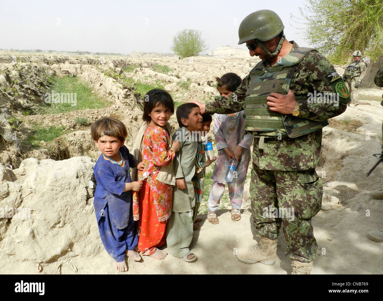 Afghan National Army Brig. Gen. Ahmed Habibi takes a break from combat operations to greet children April 1, 2012 - Stock Image