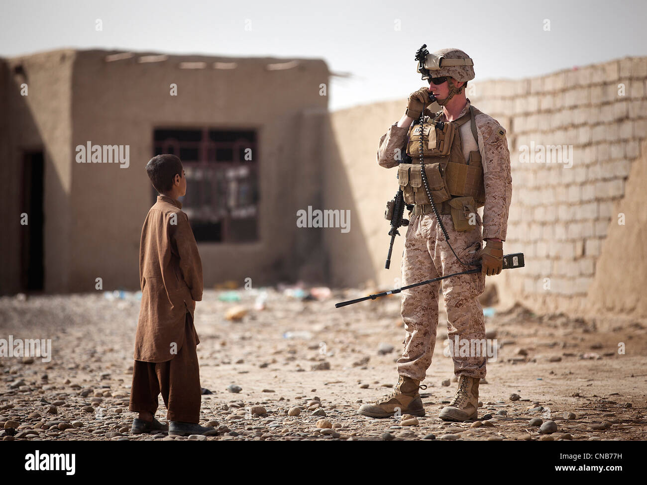 A US Marine relays a message on his radio as an Afghan boy looks on during a compound search April 1, 2012 in Garmsir - Stock Image