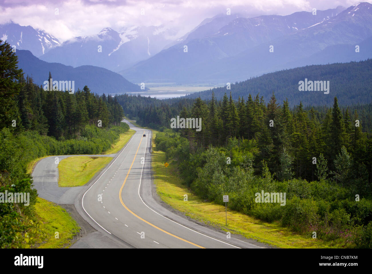 Vehicle on the scenic Seward Highway with the Chugach Mountains in the background, Kenai Penninsula, Southcentral - Stock Image