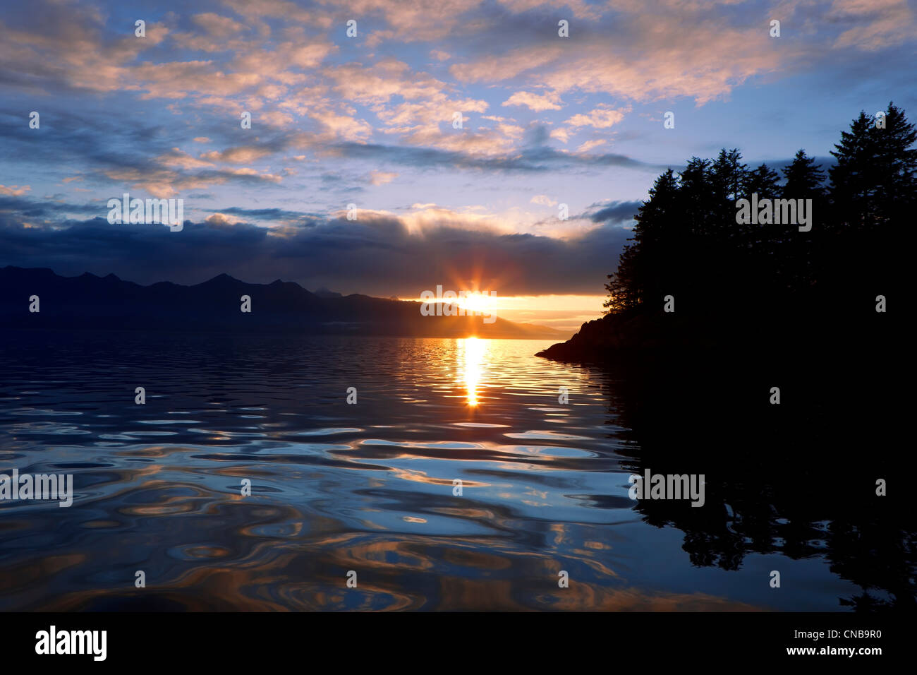 The sun sets behind Admiralty Island, Stephens Passage, Southeast Alaska, Summer - Stock Image