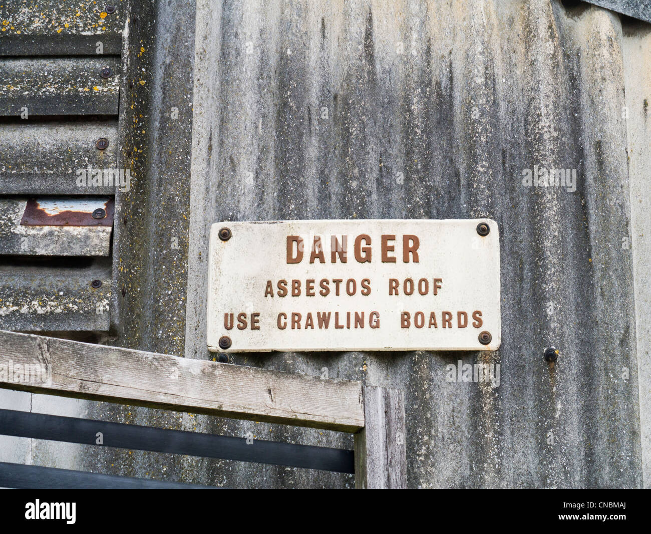 Danger Sign on an Industrial Building with Corrugated Asbestos Roof and Wall - Stock Image