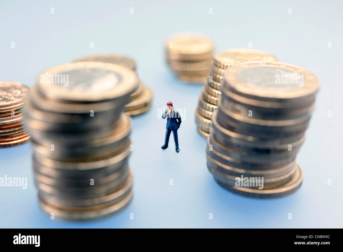 Miniature figure of a businessman surrounded Euro coins - Stock Image
